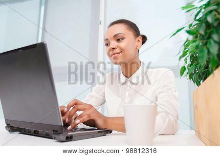 Pretty mulatto girl working on computer