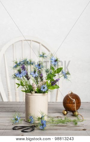 Ceramic pot filled with cornflowers with antique string dispenser