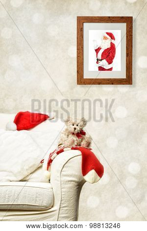 Photo of Santa Claus in wooden frame overlooking teddy on sofa