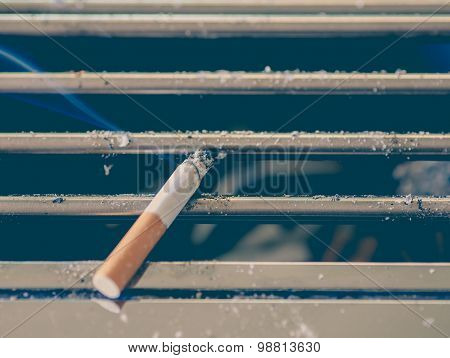 Cigarette burn on dirty metal ashtray at smoking area