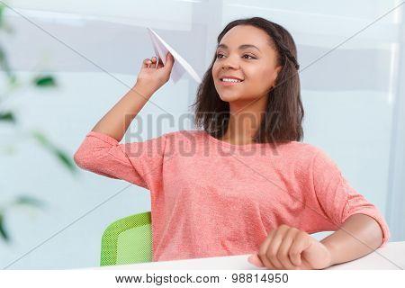 Smiling mulatto girl throwing paper plain