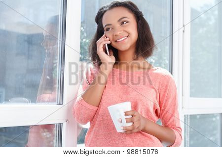 Smiling mulatto woman talking per cell phone