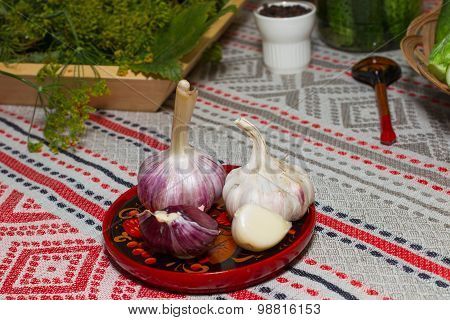 The Heads Of Garlic On A Plate Made Of Wood. Plates Painted In Khokhloma Style,  Table Cloth In Russ