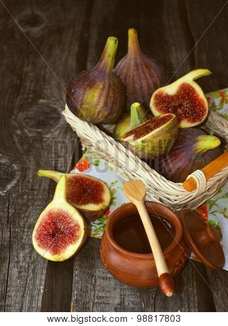 Ripe figs in the little backet  with honey in little ceramic bowl on the old wooden table
