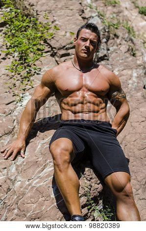 Handsome, muscular bodybuilder against white rocks