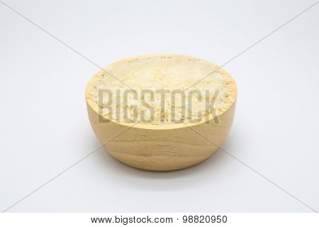 Cup of uncooked rice on wooden board