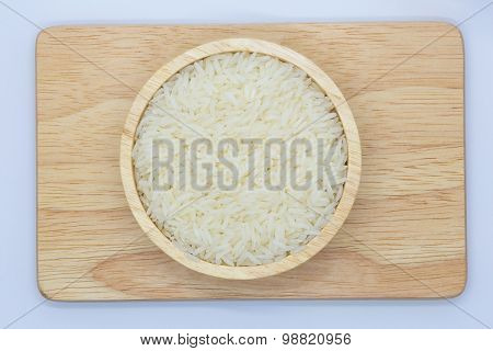 Wooden bowl with uncooked white rice o