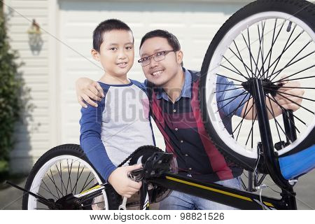 Cute Boy And His Father Repairing Bicycle