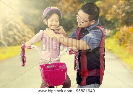 Dad Fasten Helmet On His Daughter Head