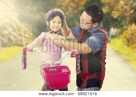 Father Helps His Daughter To Fasten Helmet