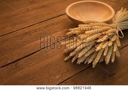 Sheaf of wheat on rustic wooden table