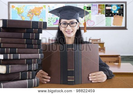Graduate Student With Mortarboard Studying In Class