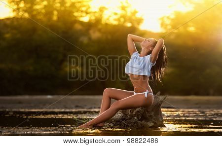 Sexy brunette in white swimsuit posing in river water. Young female in lake during sunset