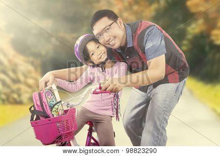 Happy Girl Riding A Bike With Dad