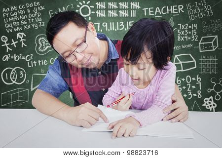 Little Girl Learns In The Class With Male Teacher