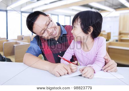 Little Girl Studying With Male Teacher In Class