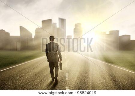 Male Developer Walking Toward A City