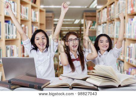 Successful Schoolgirls Raise Hands In The Library