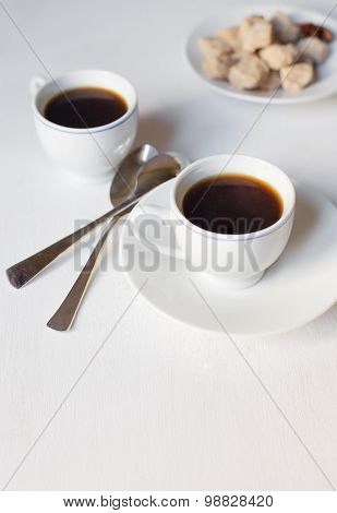 Two Cups Of Coffee On The White Table And With Two Spoons And Some Sugar