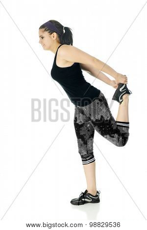 Profile of a teen girl stretching one foot behind her with the aid of both hands.  On a white background.