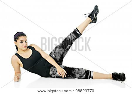 A pretty teen girl looking at the viewer as she performs side-lying leg lifts in her exercise outfit.  On a white background.