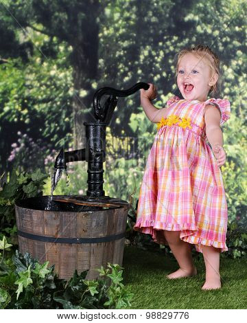 An adorable 2 year old totally delighted when she managed to get water to flow out of an old hand pump.