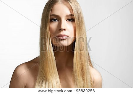 Portrait of a beautiful girl with blond hair and sparkling blue eyes on a white background