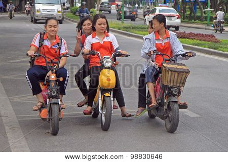 vietnamese girls are riding somewhere by motorcycle