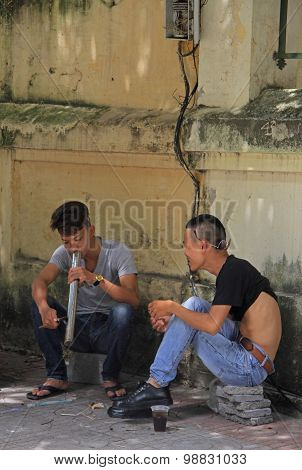 two guys are smoking something