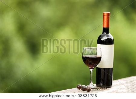 Glass Of Red Wine And Unopened Bottle Outdoors