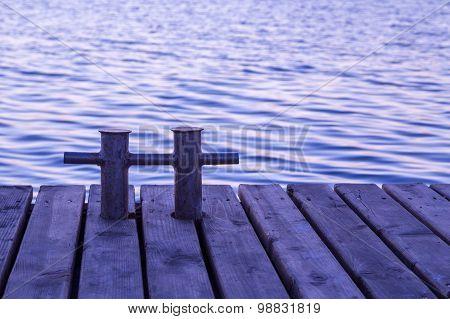 Rusty bollard on wooden pier