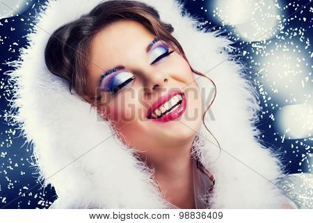 beautiful woman against blue background with snowflakes, Christmas topic