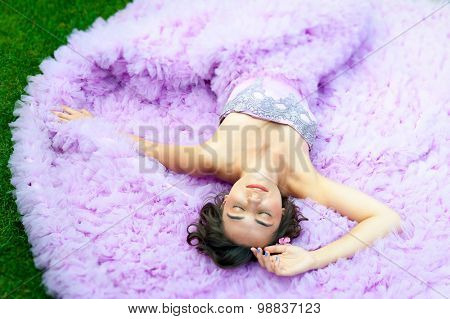 Young woman in a pink dress lying on the grass