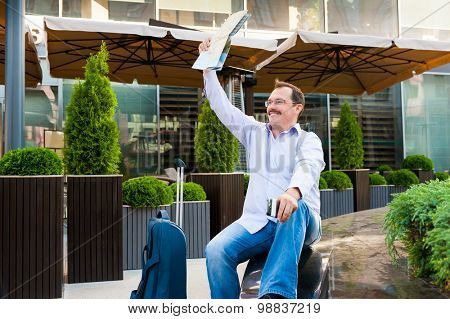Businessman waving city map to someone. He is glad to meet