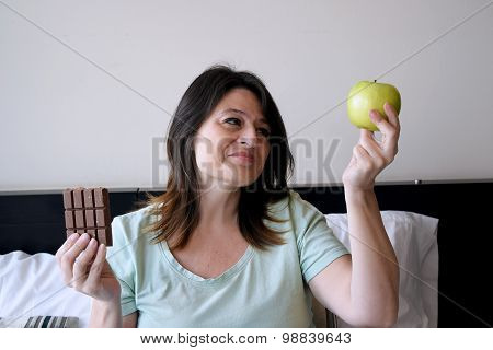 Woman Choosing Between An Apple And Chocolate