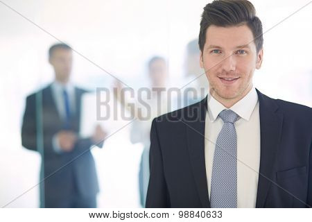 Portrait of young businessman in office with colleagues in the background .