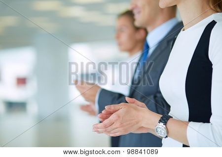 Smiling business people applauding a good presentation in the office .