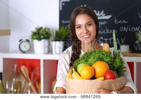 Young woman holding grocery shopping bag with vegetables .