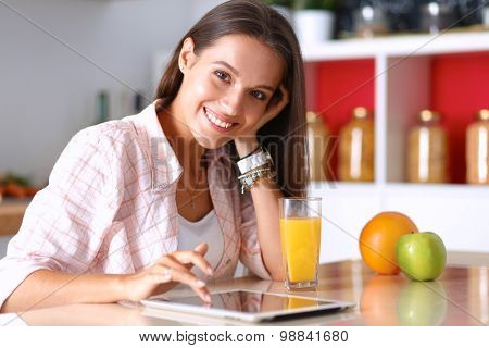 Young woman sitting a table  in the kitchen .