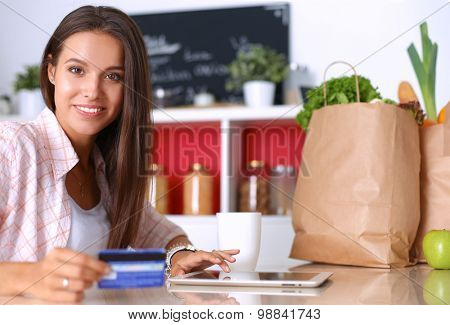 Smiling woman online shopping using tablet and credit card in kitchen .