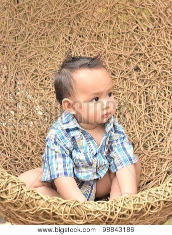 Boy In Rattan Swing