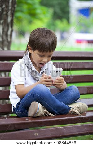 Little boy intently playing games on smartphone on a background of summer park