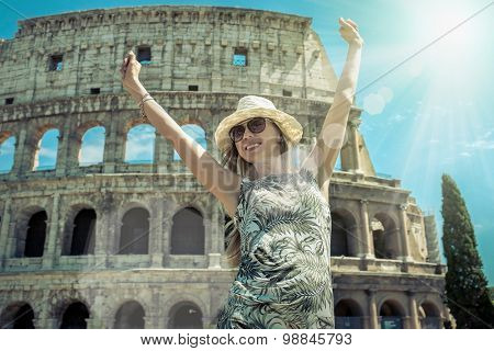 Happiness Female tourist at white hat on the beautiful view of coliseum in Rome.