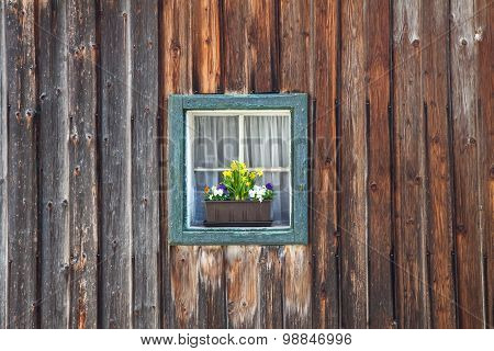 window of old wooden log house on wall background