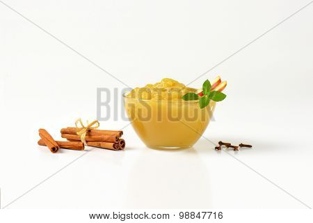 bowl of apple sauce and spice on white background