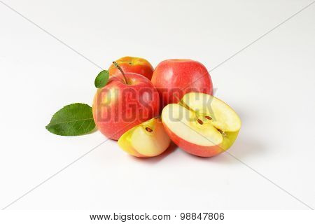 whole and sliced apples with leaves on white background