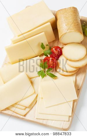 variety of sliced cheeses on cutting board