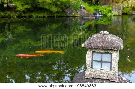 Red And Yellow Carp Fish In A Zen Pond In Japan With Lantern.