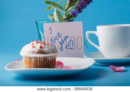 Muffin On Saucer With Flower Petal And Message