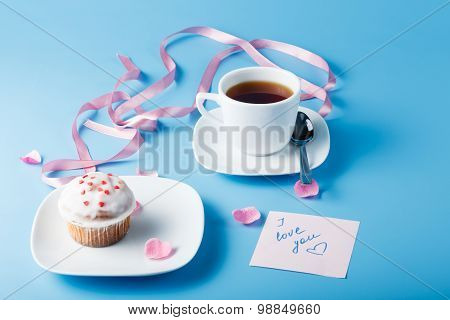 Colorful Muffin On Saucer With Flower Petal And Ribbon And Message